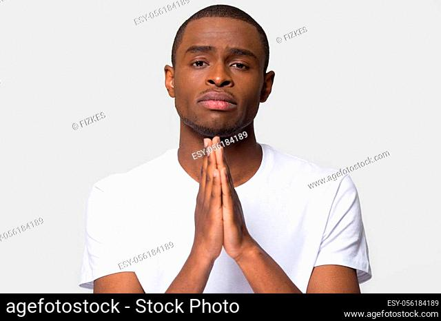 Upset African American man join hands in prayer with hope, worried unhappy young male asking for help with problems, religious Christian looking at camera