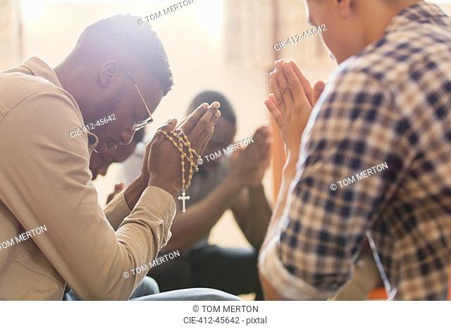 Men praying with rosary in prayer group
