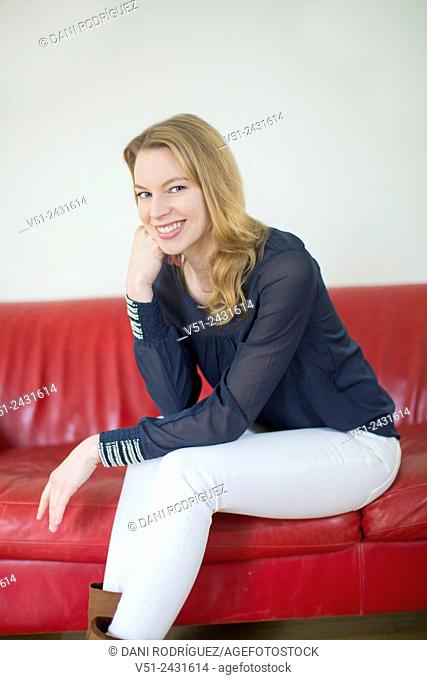 Portrait of a blonde woman sitting on the couch smiling at camera in the living room