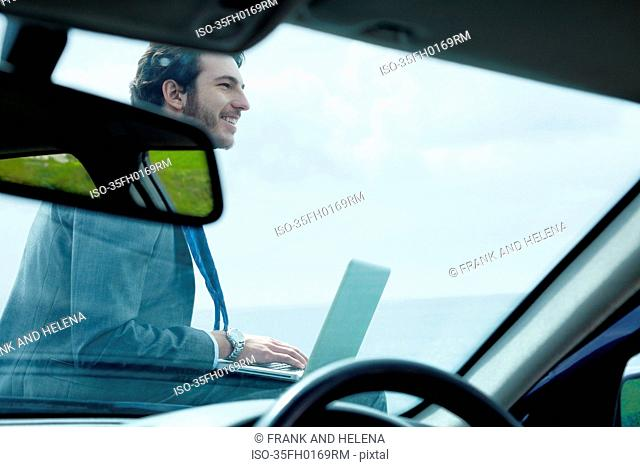 Businessman using laptop on hood of car