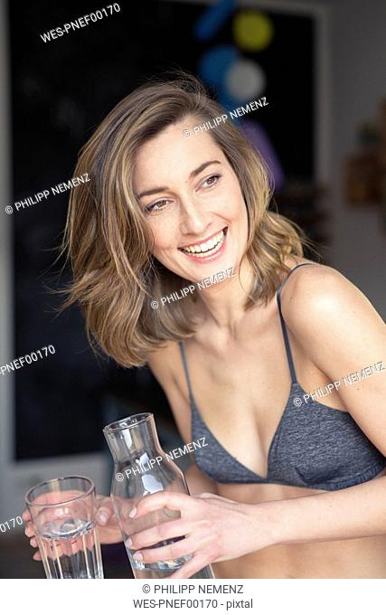 Portrait of laughing woman with water bottle and glass of water