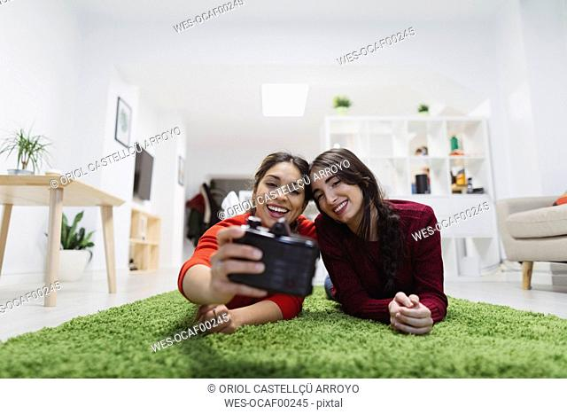 Two happy young women lying on the floor in coworking space taking a selfie