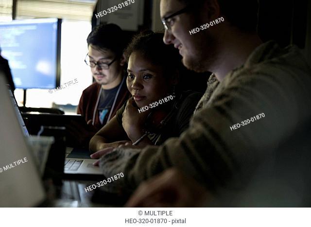 Focused hackers working hackathon at laptop in dark office