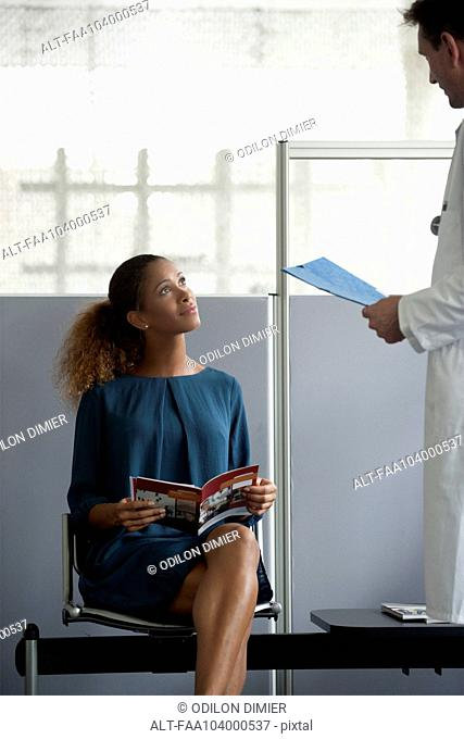 Doctor chatting with patient in waiting room