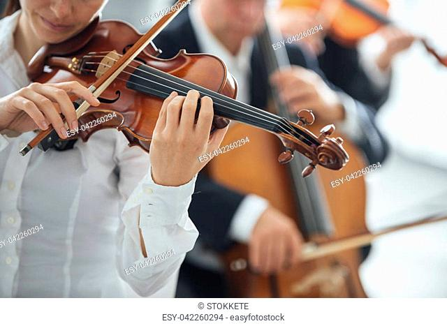 Female violinist performing and orchestra on background, selective focus, music and arts concept