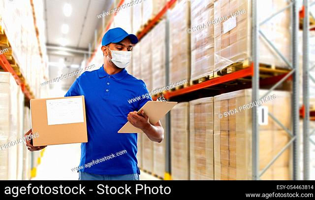 delivery man in mask with parcel box and clipboard