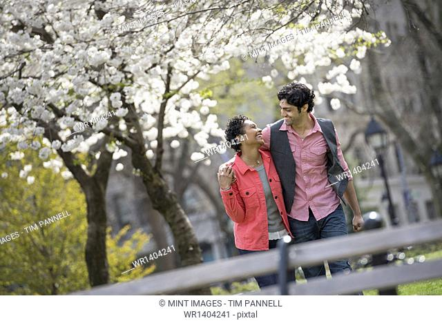 People outdoors in the city in spring time. New York City park. A couple, man and woman looking into each others eyes
