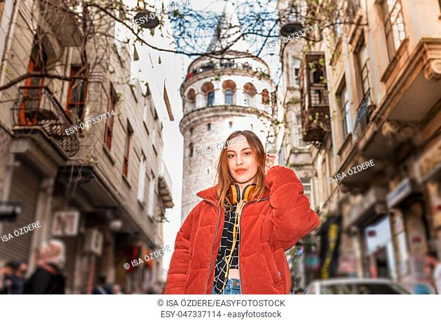 Beautiful attractive happy young trendy girl poses with view of Galata tower in Beyoglu, Istanbul, Turkey