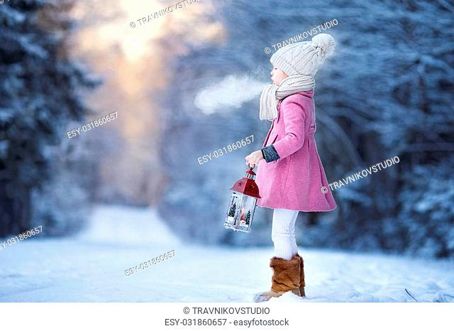 Cute little girl with flashlight having fun in winter day