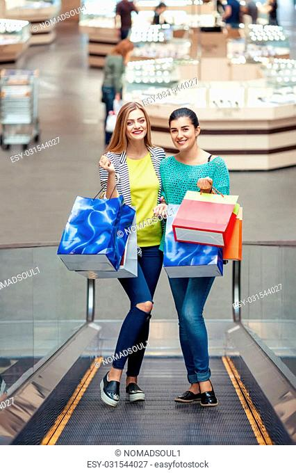 Women on the moving staircase holding bags after shopping