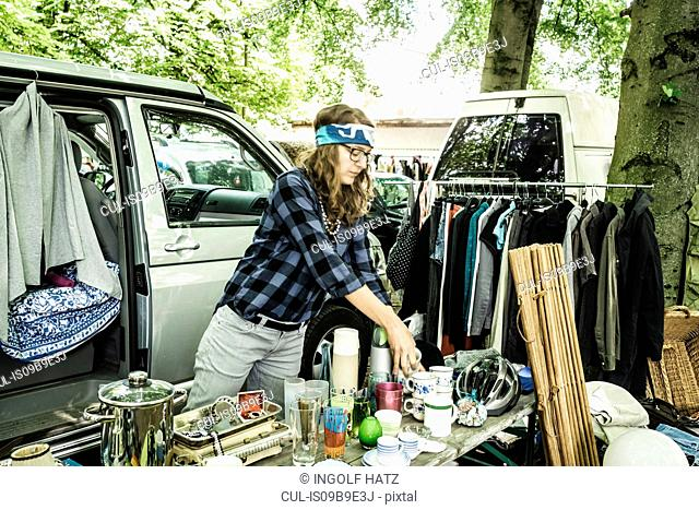 Female stall holder unpacking second hand cups on stall at forest flea market