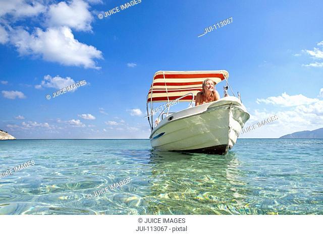 Smiling woman sunbathing on boat in sunny ocean