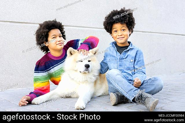 Sibling playing while sitting with dog on footpath
