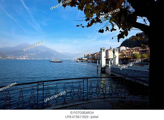 View of Bellagio lakefront in early morning sunshine, autumn colours of beech trees, passenger ferry leaving dock, mountain range visible across Lake Como