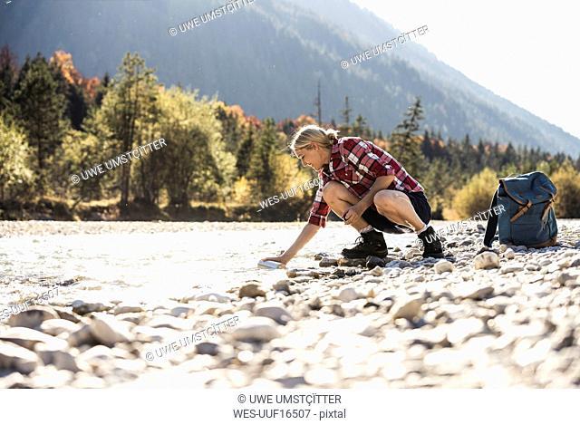 Austria, Alps, woman on a hiking trip having a break at a brook