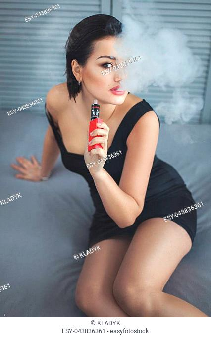 Woman smokes an electronic cigarette and exhales steam out of his mouth