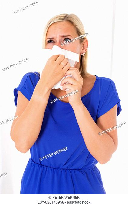 blond woman blowing her nose
