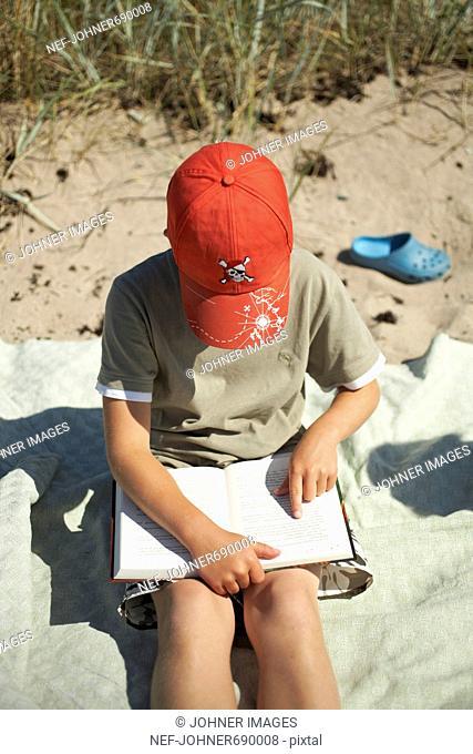 A boy at the beach reading a book, Sweden