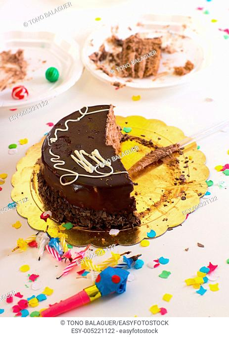 after end of child birthday party with half chocolate cake slices and confetti