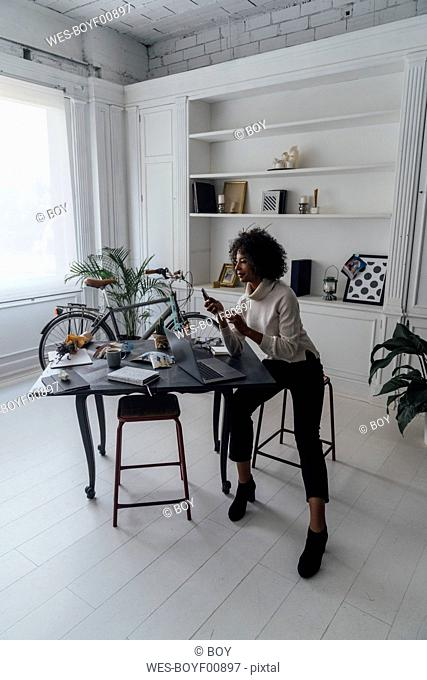 Mid adult woman working in her home office, using laptop