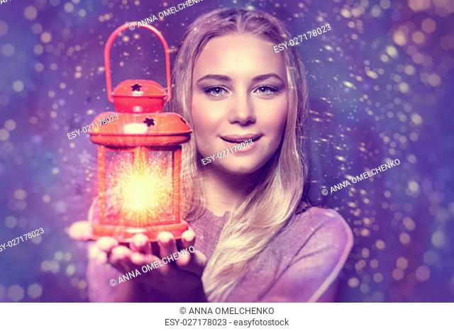 Portrait of a beautiful woman holding on hand red retro style glowing lantern over night starry sky background, magical Christmas fairytale