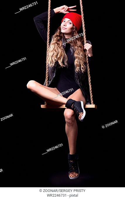 Portrait of beautiful model in red hat and jacket posing on rope swing in body dress on black background
