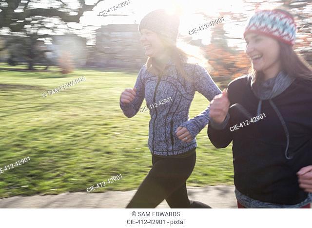Smiling female runners running in sunny park