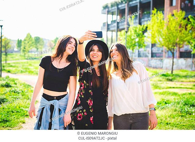 Three young female friends posing for smartphone selfie in park