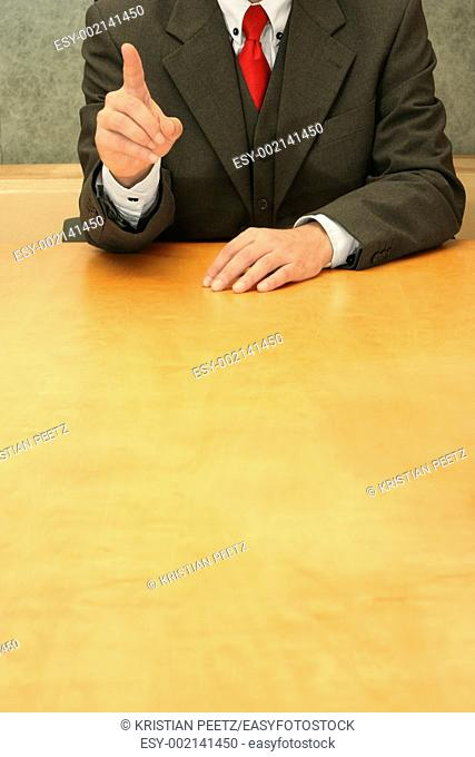 Business-man sitting at the desk, gesturing with his hand