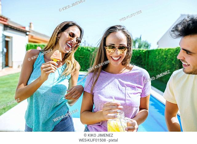 Happy friends with drink and watermelon at the poolside