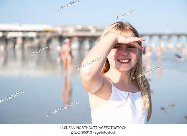Young girl on the beach shading her eyes from the sun. The background is blurred