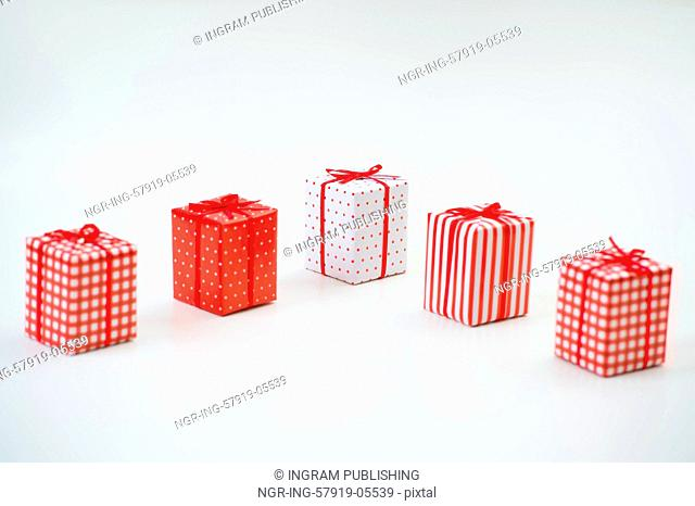 Gift boxes with xmas presents wrapped in red paper with ornament on white background