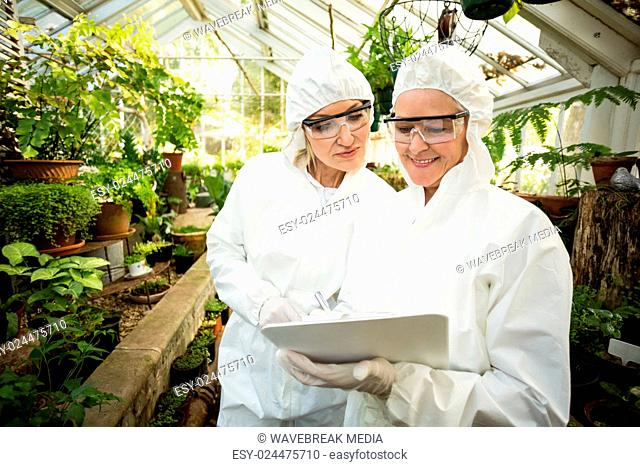 Scientists in clean suit looking at clipboard while examining plants