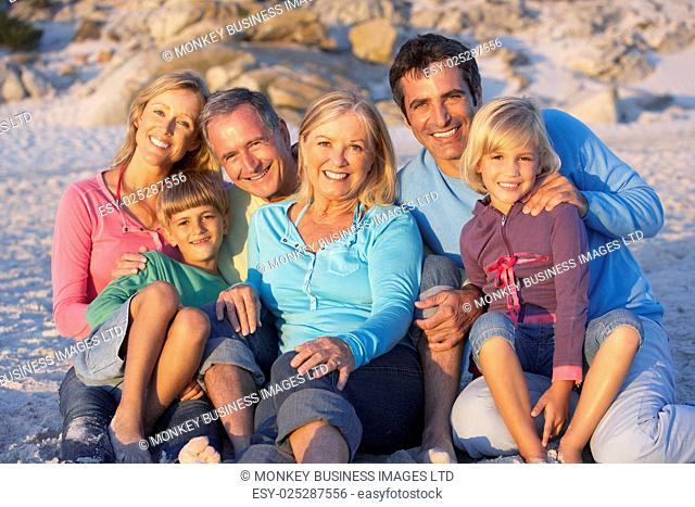 Three Generation Family On Holiday Sitting On Beach