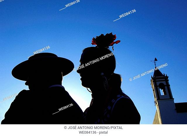 Couple of pilgrims in backlit, El Rocio, Almonte. Huelva province, Andalucia, Spain