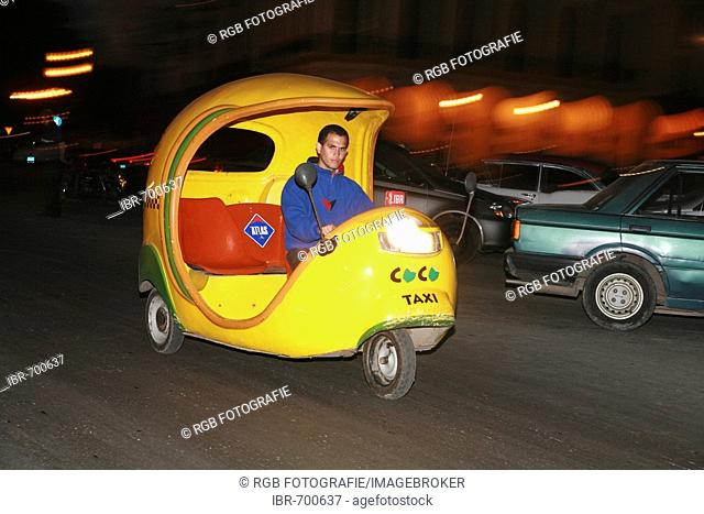 So-called coco taxi driving at night in Havana, Cuba, Caribbean, Americas