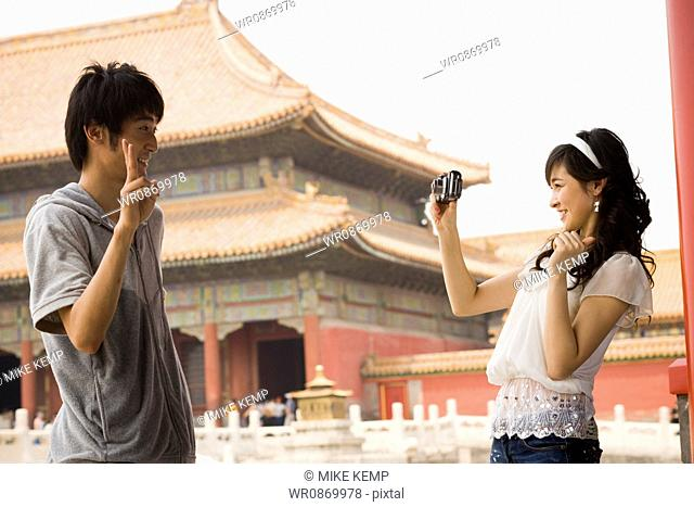 Young couple taking a photograph outdoors smiling