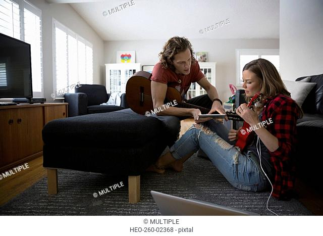 Couple with digital tablet playing guitar and ukulele