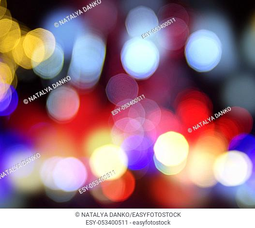 multicolored round bokeh on a black background, blurred view of the night city with illumination