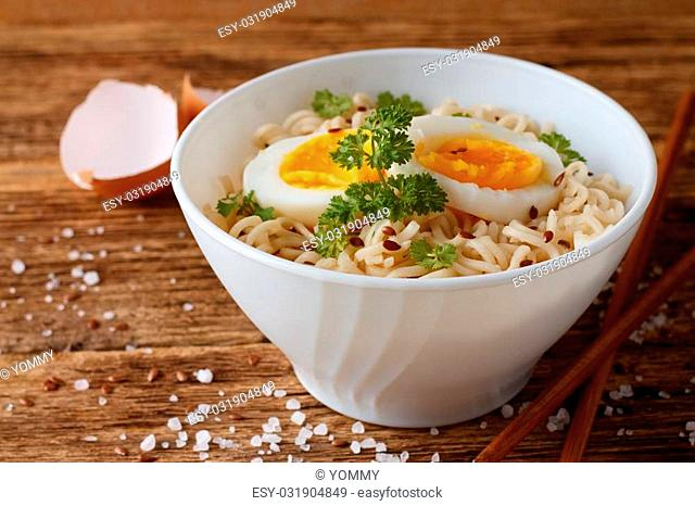 Horizontal photo of white bowl full of chinese soup with long noodles. Two slices of egg and green parsley are inside. Salt, fluxseeds