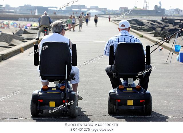 Senior citizens on motorized wheelchairs on a concrete breakwater on the beach of Scheveningen, beach district of The Hague
