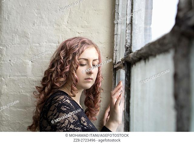 Sad woman standing by the window