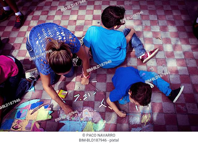 Hispanic family drawing with chalk on floor