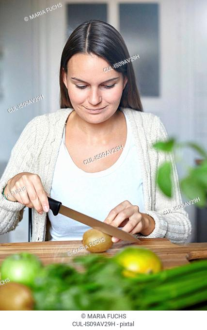 Woman cutting green kiwi on wooden table