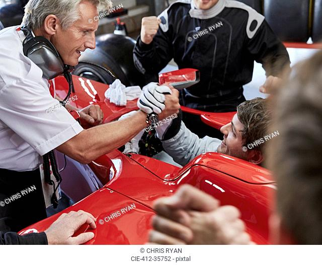 Manager and formula one race car driver handshaking, celebrating victory