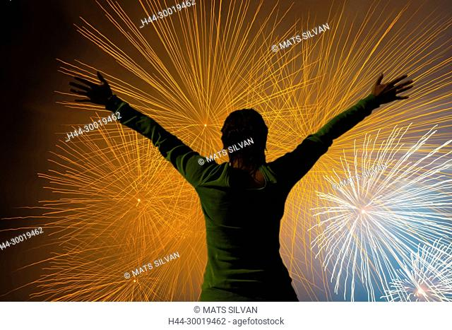Woman with Arms Outstretched Against Fireworks in Long Exposure in Ticino, Switzerland