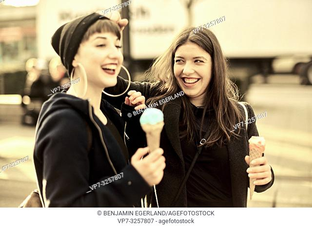 two lively friends with ice cream cones during warm winter day, in city Cottbus, Brandenburg, Germany