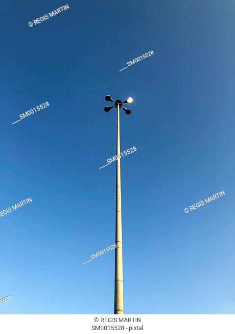 Light pole with one one light on, against a clear blue sky