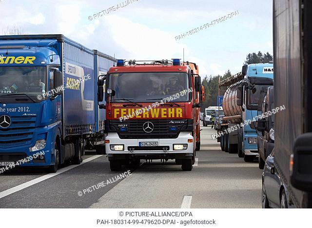 14 March 2017, Germany, Boppard: Trucks form a rescue lane for a fire service vehicle after a crash involving three trucks