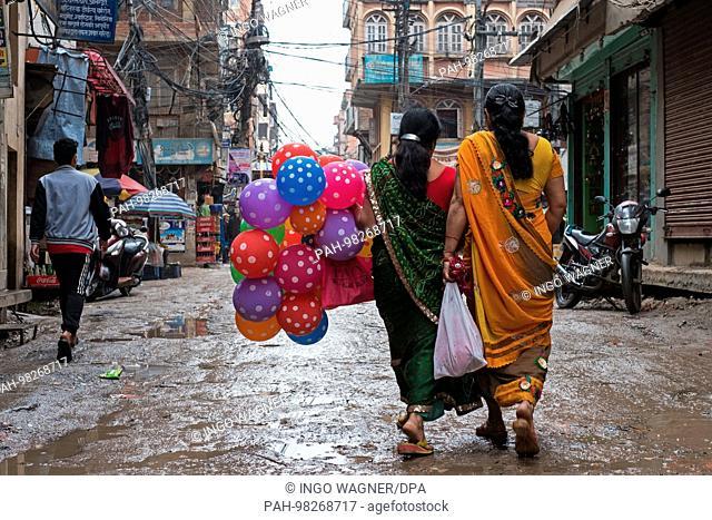 Two women goes with balloons over a rain-soaked street of the Nepali capital Kathmandu.   usage worldwide. - Kathmandu/Nepal